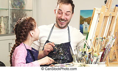 Father and daughter enjoying painting together high fiving at art studio
