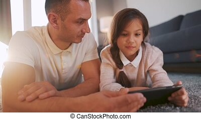 Father and daughter enjoying time together and using a tablet for family entertainment while lying on a floor in living room at home. Concept of a happy family and quality leisure time