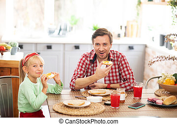 Father and daughter enjoying weekend breakfast at home