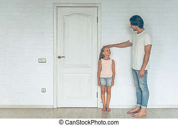 Full length portrait of handsome father measuring height of his cute little daughter near the door at home. Both are looking at each other and smiling