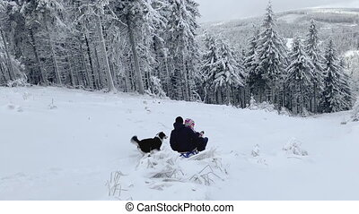 Happy father and daughter having fun riding sleigh down snow covered mountain hill in at frosty day. Man with girl go sledding. People playing with dog in winter forest. Christmas vacation.