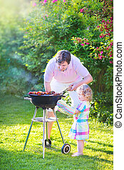 Father and daughter grilling in the garden - Young loving...
