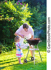 Father and daughter grilling meat