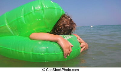 Father and daughter in Inflatable disc float at sea waves -...