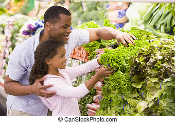 Father and daughter in supermarket produce section