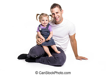 Father and daughter lay on ground having fun - A Father and...