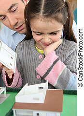 Father and daughter looking at a house model