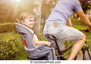 Father and daughter on bicycle in park - Young father with...