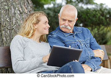 father and daughter on park bench looking at a tablet