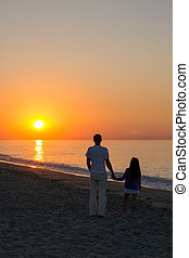 father and daughter on the beach and looking at sea