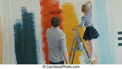 Young father and his little daughter are painting the wall in different colors. Girl is touching dad's face with brush.