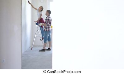 Father and daughter painting wall
