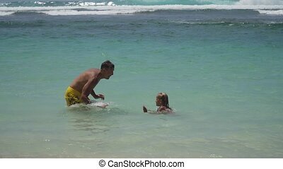 Father and daughter play on sea.