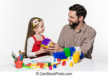 Father and daughter playing educational games together both...