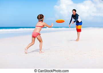 Father and daughter playing frisbee at beach