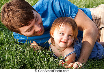 Father And Daughter Playing In Gras