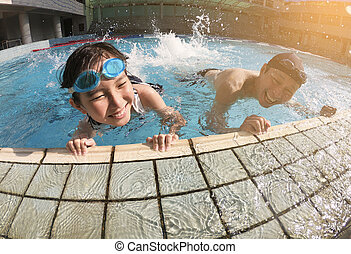 father and daughter playing in swimming pool