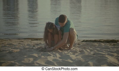 Father and daughter playing in the sand on beach