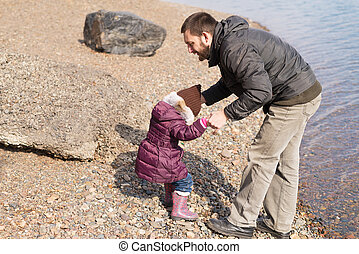 Father and daughter playing on a riverbank