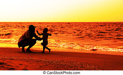 father and daughter playing on the beach at sunset