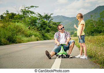 Father and daughter playing  on the road at the day time.