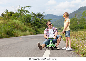 Father and daughter playing on the road.