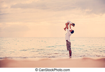 Father and Daughter Playing Together at the Beach at Sunset