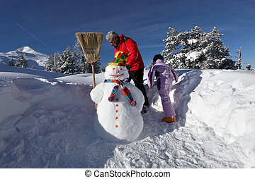 Father and daughter playing with snowman