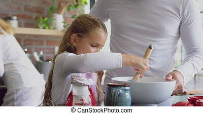 Father and daughter preparing cookie on worktop in kitchen ...