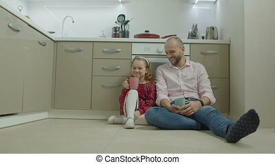 Father and daughter relaxing on floor in kitchen - Positive...