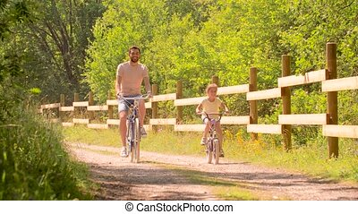 father and daughter riding bicycles in summer park - family,...