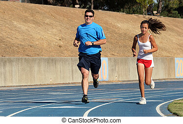 Father and daughter running on a blue racetrack