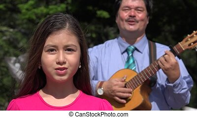 Father and Daughter Singing and Playing Guitar