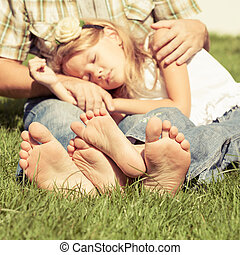 Father and daughter sitting on the grass at the day time.