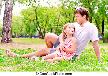 Father and daughter sitting together on the grass