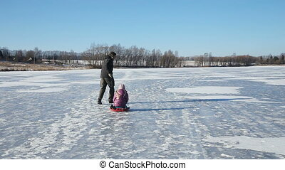 Father and daughter sledding on frozen lake