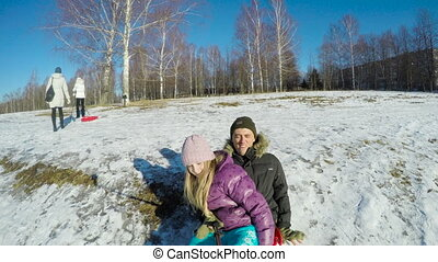 Father and daughter sledging down hill