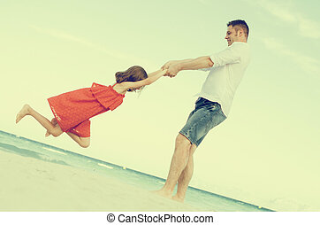 Father and daughter spinning on the beach.