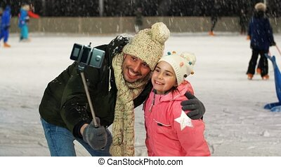 father and daughter taking selfie on skating rink - family, ...