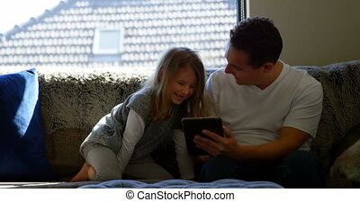 Father and daughter using digital tablet in living room 4k