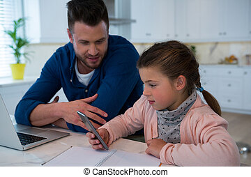 Father and daughter using mobile phone