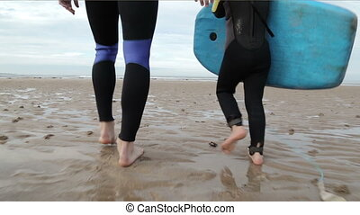 Father and Daughter Walking to the Sea to go Body Boarding