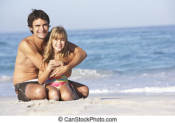Father And Daughter Wearing Swimwear Sitting On Sandy Beach