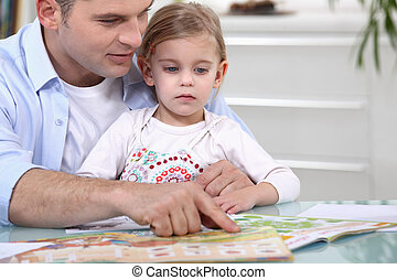 Father and daughter with a magazine