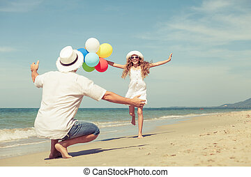 Father and daughter with balloons playing on the beach at the day time.