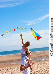 Father and Daughter with Kite on Beach - Father piggybacking...