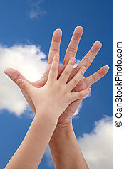 Father and daughter's hand under blue sky