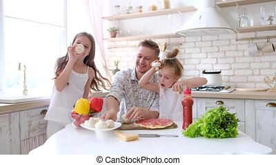 Father and daughters having a fun in the kitchen and making...