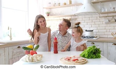Father and daughters having a fun in the kitchen with...