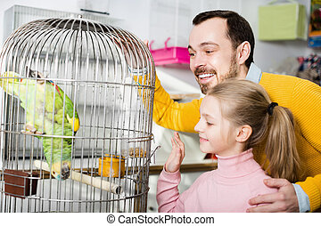 Father and girl looking at green parrot in pet store